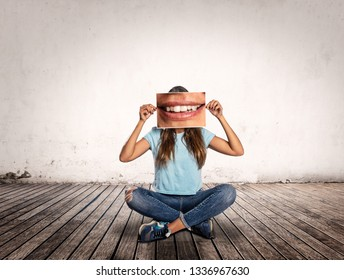 woman holding a picture of her  own mouth smiling on a room
