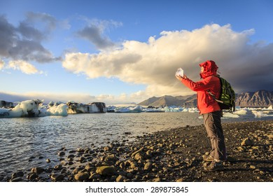 Woman is holding a piece of ice from the glacier at Jokulsarlon Lagoon in Iceland
