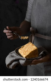 Woman holding a piece traditional napoleon cake
