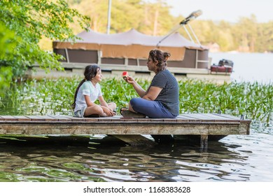 A woman is holding a piece of watermelon is talking to her young daughter while sitting on a dock