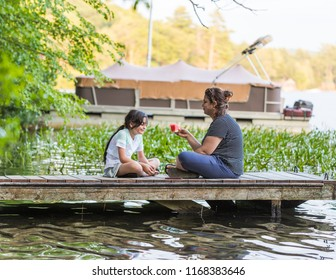 A woman holding a piece of watermelon is talking to her young daughter