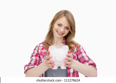 Woman holding a piggy bank against a white background