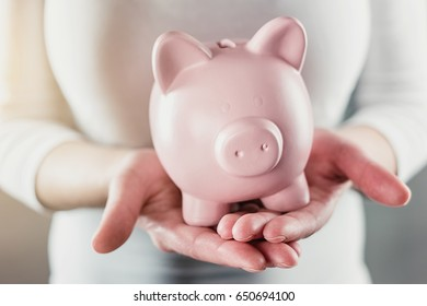 woman holding a piggy bank - money investments concept image
