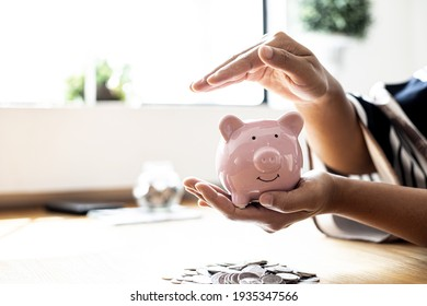 A woman holding a piggy bank in the shape of a pink pig, she is organizing money to divide it into savings and buy funds to make it grow. Personal finance concept.