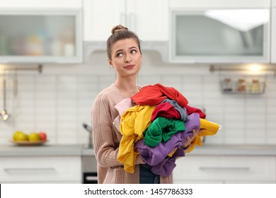 Woman holding pile of dirty laundry in kitchen