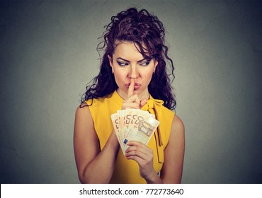 Woman holding pile of euros and asking for silence while practicing corruption.