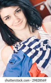 Woman holding pile of laundry smiling