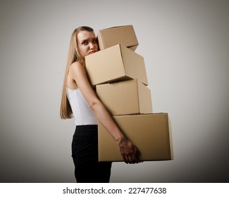 Woman holding a pile of packaged parcels. Woman doing something.