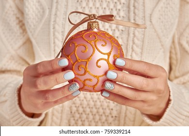 Woman holding a pink bauble with curly pattern. Glittering decoration and cute bow on cap. Tis the season to be jolly.
