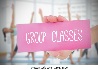 Woman holding pink card saying group classes against fitness class in gym