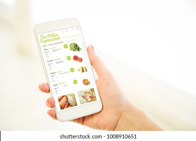 Woman holding a pink gold generic smartphone showing online supermarket
