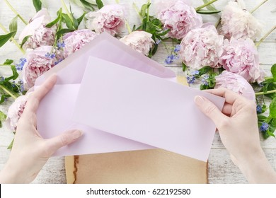 Woman holding pink sheet of paper and envelope. Pink peonies and forget me not flowers on white wooden background, copy space.