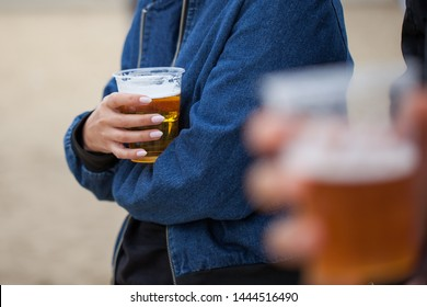 Woman holding pint beer in the plastic cup on the beach outdoor at the festival event, concert