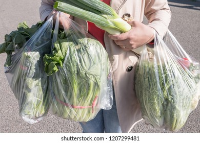Woman holding a plastic bag of vegetables