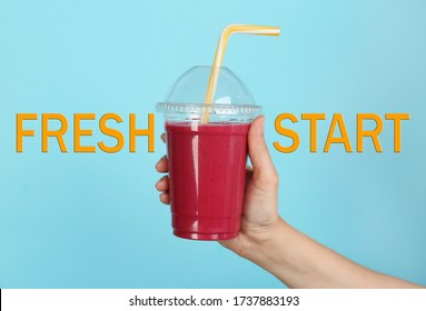 Woman holding plastic cup with smoothie and phrase FRESH START on light blue background, closeup