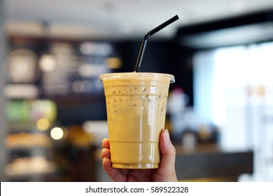Woman holding plastic glass of iced coffee with milk on blurred background