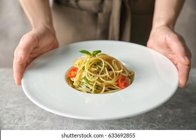 Woman holding plate with delicious pasta