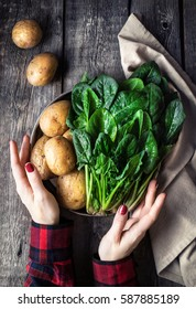 Woman holding plate with potatoes and fresh spinach on rustic wooden background in the kitchen