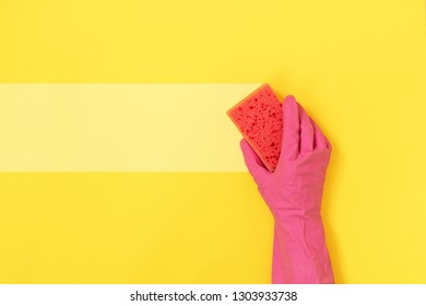 Woman holding polyurethane dish sponge for washing in hand with pink rubber gloves isolated on yellow background with empty space for text