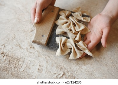 Woman holding a portion of just prepared raw farfalle pasta at a restaurant