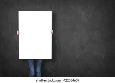 woman holding a poster over a blackboard