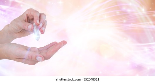 Woman holding precious gem against glowing background
