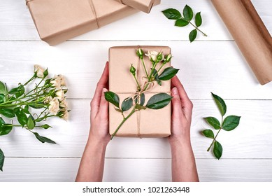 Woman holding present box with roses on white wooden table background, free space. Close up of gift box in girl's hands, copy space. Holiday background. Flat lay, top view. Gift wrapping background