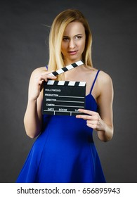 Woman holding professional film slate, movie clapper board. Hollywood production objects concept. Studio shot on black background.