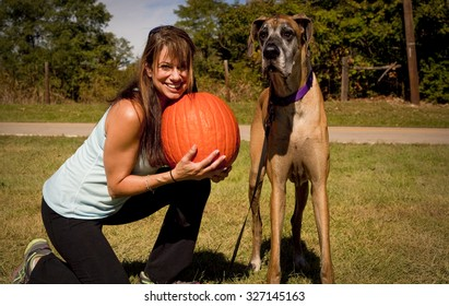Woman holding pumpkin squatting next to her great Dane