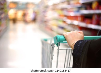 a woman holding pushcart shopping in supermarket in mall in Saudi Arabia Gulf Middle East