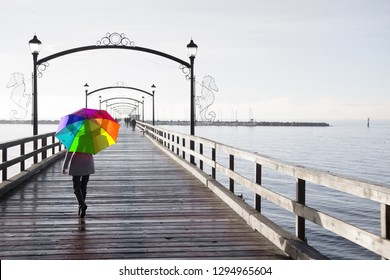 Woman holding a rainbow colored umbrella walking on a rainy day on the pier in White Rock, British Columbia, Canada.