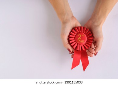 Woman holding a red 2nd place winners rosette cupped in her hands over white with copy space conceptual of winning, championship, competition, success or a challenge