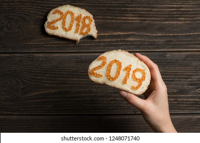 Woman holding red caviar 2019 sandwich with 2018 sandwich bitten on the background. The taste of passing 2018 and coming new year.