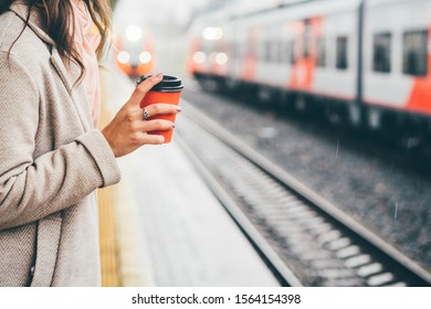 Woman holding red cup and drinking coffee during waiting the train at the station. Close up hand with paper cup.