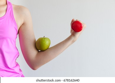A woman holding a red dumbbell for exercise and training, red apple on an arm for healthy life style