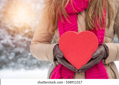 woman holding a red heard in winter landscape outdoors