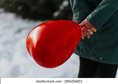 woman holding a red heart shaped balloon from the back