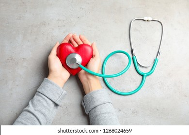 Woman holding red heart and stethoscope on gray background, top view. Cardiology concept