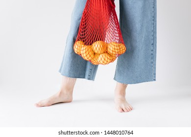 Woman holding a red string shopping bag with lemons. Concept of ecology, environmental protection.