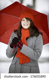 A woman holding a red umbrella in the snow.
