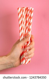 Woman is holding red and white paper straws in hand on bright background. Event and party supplies. Earth pollution concept. Copy space