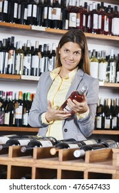 Woman Holding Red Wine Bottle In Shop