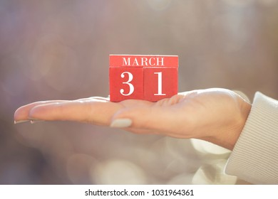 the woman is holding a red wooden calendar. Red wooden cube shape calendar for MARCH 31 with hand