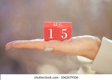 the woman is holding a red wooden calendar. Red wooden cube shape calendar for AUG 15 with hand
