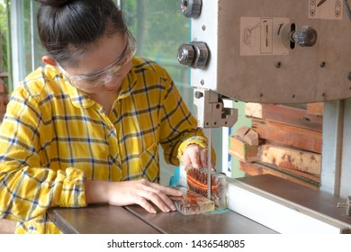 Woman holding resin pine cone for check over, Carpenter standing is craft working cut resin pin cone at a work bench with band saws power tools at carpenter machine in the workshop