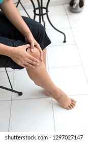 Woman holding right knee with her two hands indicating discomfort