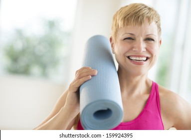 Woman holding rolled up exercise mat at gym