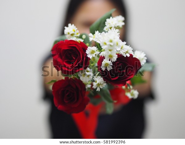 woman holding roses in front of her face