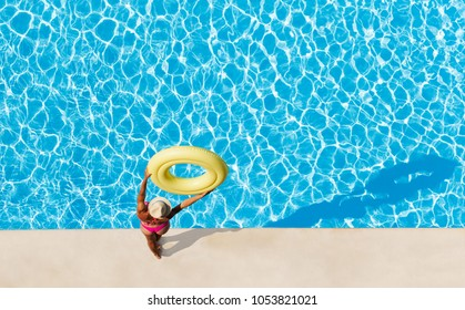 Woman holding rubber ring overhead at poolside