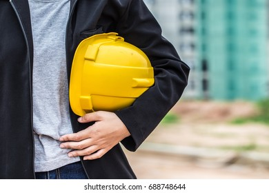 Woman holding safety yellow helmet in construction site